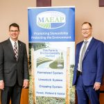 Pictured (left to right) Chief Matt Lohr, USDA Natural Resources Conservation Service, a banner sign, and Director Gary McDowell, Michigan Department of Agriculture and Rural Development.