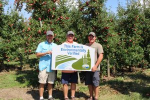 three men holding a sign in from of apple trees
