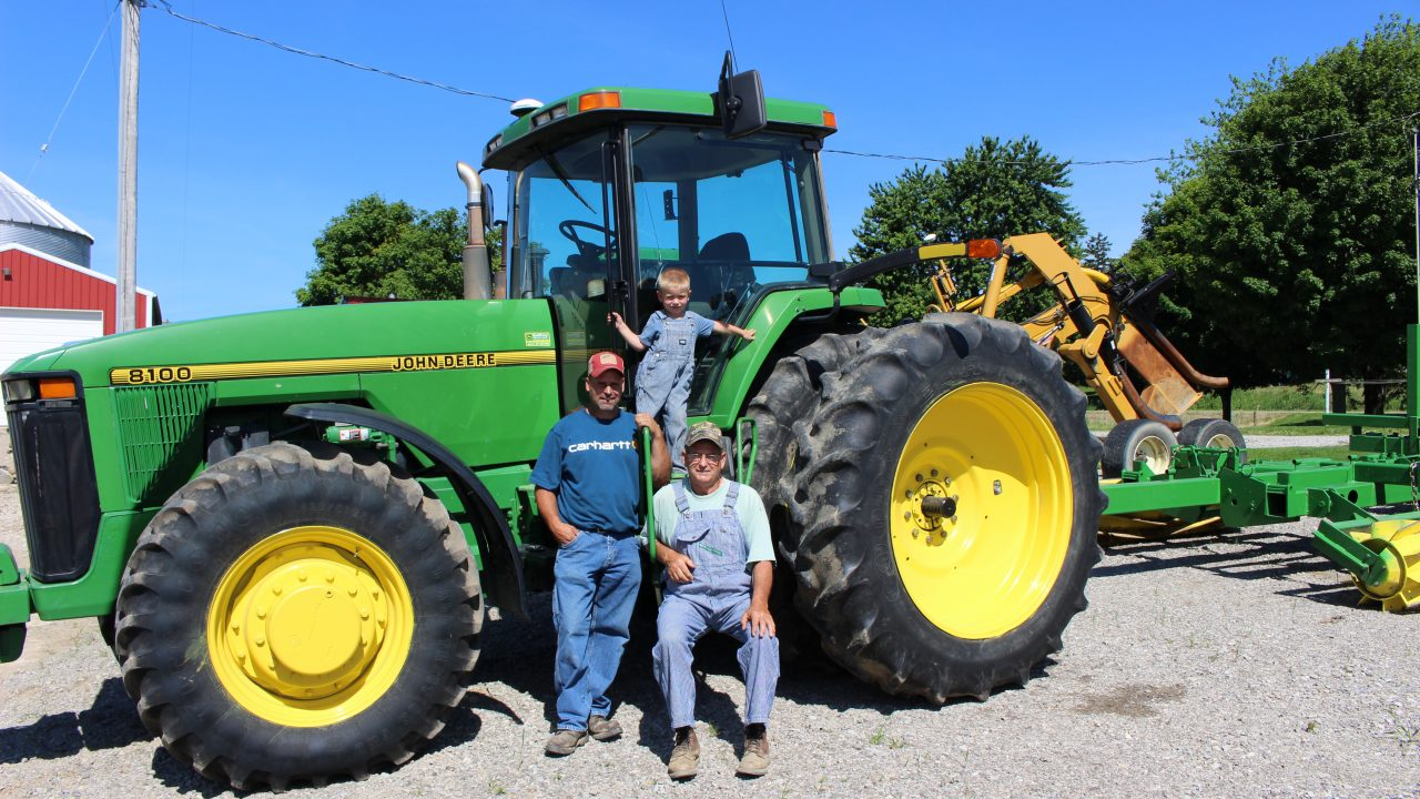 two men and a boy standing next to a tractor