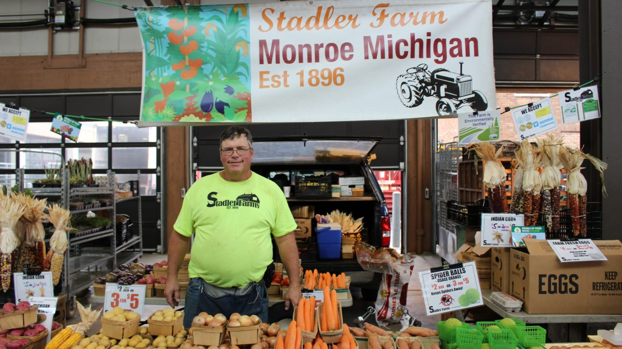 man at farmer's market with a sign above his head that says Stadler Farms.